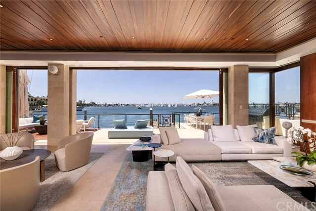 Artfully positioned at the southern west facing side of Newport Beach's private bay-front enclave Linda Isle this property showcases premiere unobstructed views of Newport Harbor's Bay & Lido Island over the nautical activities of the primary turning basin to the Balboa Peninsula with year round sunsets in the back drop. The recently upgraded property originally constructed by Fleetwood Joiner boasts clean lined soft contemporary architectural elements that blend into the tonal calming interiors. This secure home offers every technology in home automation and security assisting in making this home serve its owner. Once inside you are greeted by the three story custom water installation that wraps seamlessly around the stair casing offering tranquility that resonates throughout ending in the lowers levels teak clad home spa equipped with hot/ cold plunge all illuminated by the soothing amber glow of the Himalayan Salt adorned sauna / meditation room. The main level plays host to the two car garage, guest suite, foyer, formal sitting room, dining room, and kitchen overlooking the main bay facing great room that spills out to the outdoor deck and dock that can accommodate up to an 80 foot vessel. The upper levels skybridge navigates you to the gym, secondary guest suite, service/ laundry room and primary bedroom retreat with ensuite massage therapy room and balcony highlighting the panoramic breathtaking views. All located within Linda's Isle's charming neighborhood which offers its owners 24/7 guard gated security, wide peaceful boulevards with rare ample parking and a strong feeling of community.