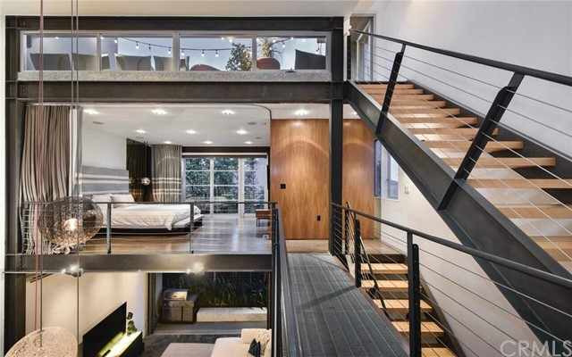 """This stunning modern loft by award-winning local architect Steven Ehrlich, AIA offers panoramic ocean views and sophisticated interiors by designer Jae Omar, just moments from the beach, Venice Boardwalk, Abbot Kinney and Rose Avenue. Come up from the beach and pass one of the main film sites for well-known TV show """"Californication."""" Enter the secure gate with 4 architectural units leading to this corner unit's open, airy interiors with soaring ceilings and 2.5 story art wall. A light-filled living room features polished concrete floors, expansive windows, large fireplace and a pull-up garage door window that brings the outside ocean air in. A custom chef's kitchen is outfitted with Viking stove, oversized Sub-Zero fridge and custom cabinetry. Suspended over the living room, the master suite features a showroom closet and large master balcony. Both bedrooms offer the option for communal living with no walls or complete privacy by closing the dividers. A private entertainer's rooftop deck with corner ocean views of Catalina and Point Dume fosters a seamless transition between the levels of the loft and the grand finale with sunset facing soaking tub. This unit also comes equipped with full surround sound throughout the house; recently remodeled bathrooms; security system; side-by-side direct access garage which can be used as gym; guest parking for multiple cars; in-unit laundry. 25 Brooks exemplifies modern coastline living in one of L.A.'s most dynamic enclaves."""