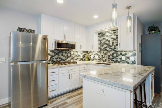 """You will love this one-of-a-kind studio that has been designed to maximize the living space to the fullest. This beautifully decorated studio looks like a model unit with the custom tile floors throughout and custom windows that bring in wonderful natural light. The gorgeous kitchen boasts quartz countertops accented with a beautiful backsplash, all new custom cabinets, a breakfast bar, all new appliances including refrigerator, microwave, and gas cooktop.  The spacious bathroom has been designed with a large walk-in shower.  Other features include a wall-mounted 65"""" TV, a Mini-Split A/C and Heating, garage parking, and plus utilities included (gas, water electric, wi-fi and cable). Tenant can enjoy the community features including swimming pool, Jacuzzi, and tennis courts."""