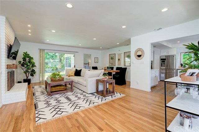 Large living/dining area with wood floors and recessed lighting