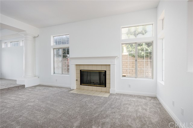Step down into this large and bright living room with a gas fireplace.