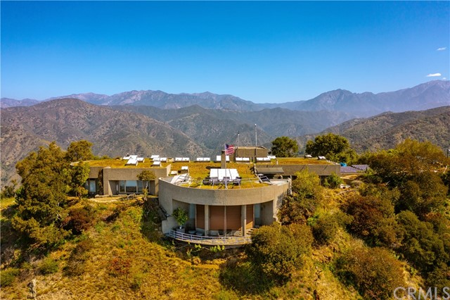 """Presenting one of the most stunning and private estates in all of Southern California!  Perched on 73 acres, and encompassing over 5000 square feet this 4 bedroom 3 bathroom fabled home that many have longed to see since its construction in 1990, features the ultimate in seclusion and privacy.  While only being minutes from the charming Glendora Village, top rated schools, and much more.  Work in Los Angeles or beyond? Commute right from this homes private helicopter pad!  Situated at the end of the prestigious Bluebird Ranch behind two separate security gates, this estate is surrounded by Conservancy land, and National Forest, which ensures you a lifetime of nature and space.  The views are absolutely unparalleled especially at this 2600 foot elevation above the city.  Take in sweeping views of the valley and twinkling city lights, ships sailing off the  Orange County and Los Angeles coast lines, the fire works at Disneyland... see Mt Palomar in the distance, and incredible views of Mt. Baldy and Wrightwood.  Step inside this epic space, and you'll see a home that was tastefully and thoughtfully designed and engineered by AC Martin Partners as an art piece in harmony with the land.  Passive solar design uses skylights and walls of glass cleverly designed to take advantage of the sweeping views and breezes that cool the home.  18 inches of earth on the roof help keep the house comfortable all year long and allow for a memorable roof top garden to take in the truly 360 degree views.  A main """"Great Hall"""" sets up what is a breathtaking experience inside and leading you to three separate wings containing the massive living room, library, office, game room, and bedrooms.  Enjoy airplane-like views, and natural beauty from multiple decks and the rooftop as you wait for the helicopter to pick you up and take you out for a night on the town.  This is one of the most special and unique estates to hit the market and it offers a living experience like no other."""