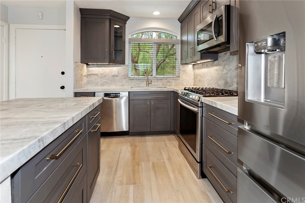 This completely remodeled unit is just minutes from El Niguel golf course, Salt Creek Beach, Dana Point harbor and Laguna Beach.  This is a rare desirous single level unit with a direct access 2 car garage with custom built in shelves for ample storage.  It has a large laundry room below the living area for added privacy.  It has been totally remodeled with PEX piping, all new windows & doors, hardware, all new led lighting, new water heater, new digital fireplace, new custom powder coated wrought iron stair railing mirror wardrobe doors, new high quality variable ceiling fans with adjustable lighting. Enjoy the permitted kitchen remodel with high quality cabinets, appliances, under cabinet lighting, exotic stone countertops and backsplash, an island and a large peninsula with seating for 4 people.  It has new Italian porcelain commercial grade plank tile flooring throughout.  Both bathrooms were completely remodeled with the highest quality materials.