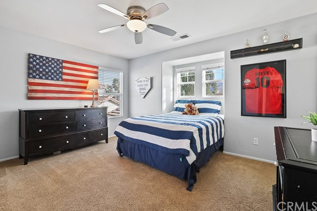 Spacious bedroom and updated ceiling fan, with large windows bringing in natural light.