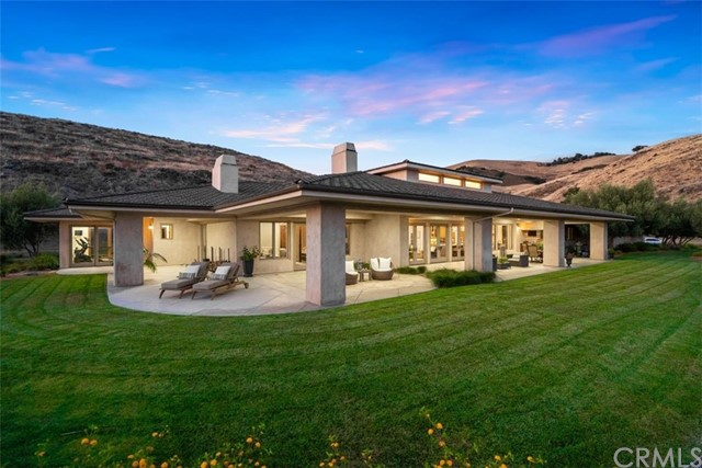Exquisite Edna Ranch Estate! This breathtaking single-level custom home is ideally sited on a 1.5+ acre elevated parcel, overlooking the dreamy Edna Valley and beyond. Sunsets are beyond compare thanks to the incredible outdoor living areas, designed in the style of some of Hawaii's finest oceanfront estates. With more than 3,000 SqFt of Lanai style patios and verandas surrounding the home, you may have a hard time deciding on your favorite exterior space! Fastidiously built in 2008, the execution and finish of this 5,400 SqFt residence will not disappoint. From the elegant Santa Barbara stucco finish and unique 'shake tile' roof, this home exudes QUALITY.  Inside, you'll find rich stone and wood floors, 10' volume ceilings, contemporary lighting and elaborate built-ins. The impressive Great Room offers lofty 17' ceilings and a trio of clerestory windows for added natural light, plus a custom stone surround Fireplace Xtrordinair (one of FOUR fireplaces in the home). The kitchen is equally impressive with a HUGE marble island, abundant storage and high-end appliances. Equally stunning, the master suite - complete with its own private patio areas, dreamy bathroom with heated stone floors... and a GYM! Every bedroom is an en-suite - one of which rivals the master with its own fireplace, walk-in closet and patio area. And the garage - at nearly 1,700 SF, it will easily accommodate 5-6 cars (if tandem parked), and has seemingly unending storage.  Be sure to check out the video!