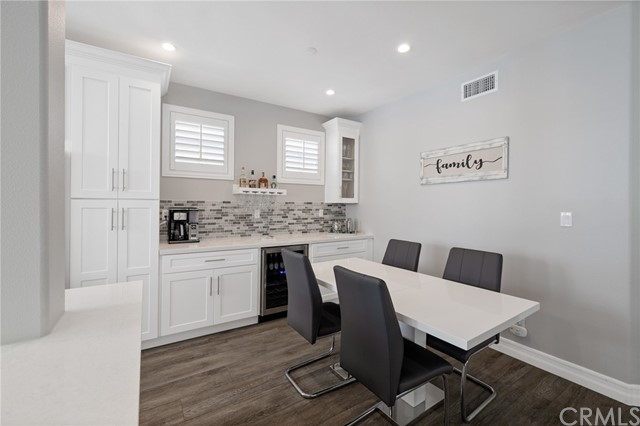 dining area with additional cabinetry, bar area, and wine fridge