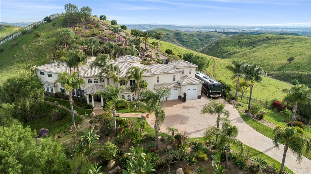 This amazing custom built estate is located on 2 of the most incredible acres you will ever see. The breathtaking panoramic  views of Catalina, city lights, sunsets and surrounding hills are truly magical.  When entering the gates you immediately know you are in for a special treat. The privacy and views high atop Copa De Oro are unlike anything else. When entering the foyer, the sheer size and openness of the home is impressive.  The nearly 7,000 square feet has 5 bedrooms 5.5 baths, library, office and movie theater.  The gourmet kitchen has custom cabinetry, granite counters, Thermador appliances and the oversized island makes this perfect for entertaining.  The ground have been meticulously maintained and make you feel as if you are living in an amusement park. The pool has 3 waterfalls, 2 beaches, spa and a massive water slide.  The covered patio with built-in barbecues is also another great place to entertain and take in the sights and surroundings.  The 6 car garage/workshop also has full RV hookups is perfect for any car or monster garage lover. And all this privacy is just minutes from Brea's award winning schools, Whole Foods, fine dining, theaters and Down Town Brea.