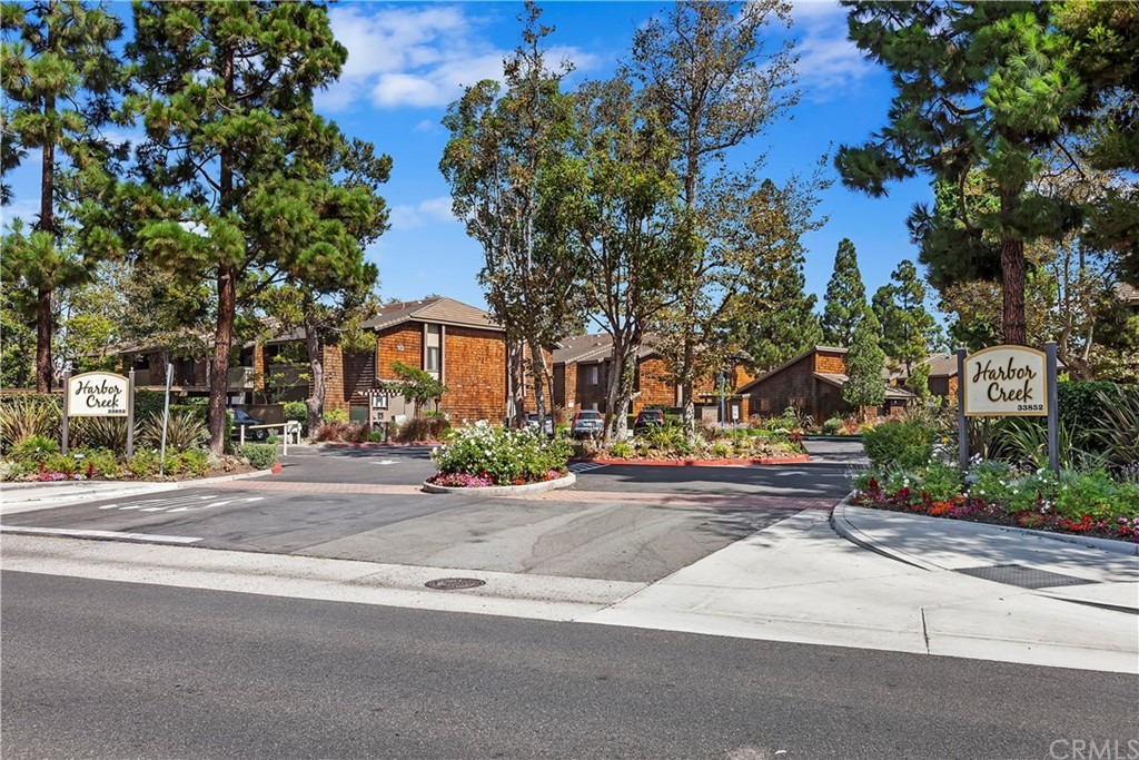 Well located and desirable controlled access Harbor Creek community within a convenient distance to the sand at Doheny State Beach/Park and Dana Point Harbor.  Well maintained community and pristine landscaping.  Quiet end unit with the sounds of running streams and soothing ponds encompass this very private upper unit with high ceilings.  Gentle ocean breezes and views of the streams from the outside deck. You can fall asleep from the sounds of the streams outside your bedroom window.   All new rich warm cabinets in the bathroom and kitchen. Both feature granite counters and all new fixtures & lighting.  New LCD recessed lighting in kitchen, new electric range, microwave, garbage disposal, newer dishwasher and includes new refrigerator.  There are 3 ceiling fans, a walk in closet and new air conditioning unit.  Outside on the deck find the laundry closet that fits a full size capacity washer & dryer.  Your carport is located a convenient distance at the rear of development, Space #223.  Just behind Harbor Creek is a gate off of the parking area to Sycamore Creek Park and trail. There is a children's play area and terrific trails that will take you to the beach in a few minutes. The HOA covers the water (including hot), trash, sewer & gas.  Located off the gated pool & spa is a community laundry & sauna.