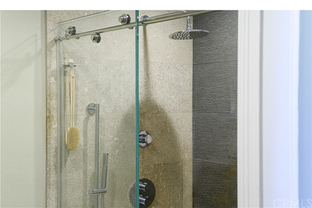 Modern shower with stone enclosure and frameless sliding-glass door