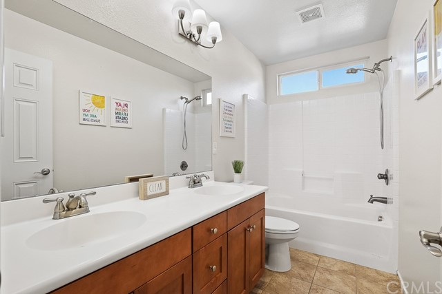 Large bathroom with dual vanity sink, combo shower/bathtub. Also just freshly painted!