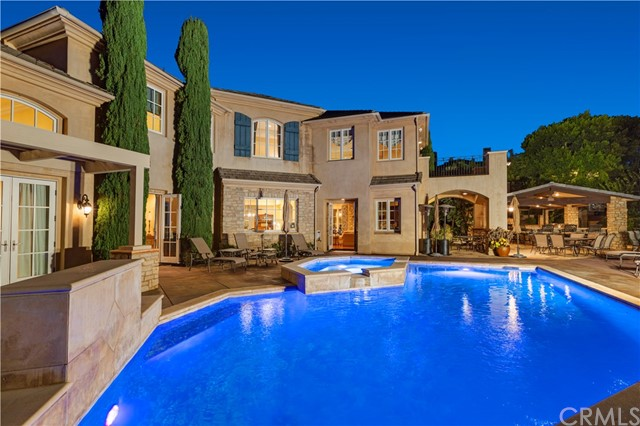 North Tustin is known for its gorgeous tree-lined streets, charming custom homes, and excellent schools. Situated in a premium location in the coveted upscale neighborhood of Lemon Heights, discover this grand estate in the hills. With over 6900 SF of interior living space positioned on half an acre of land, savor endless views and amenities in this extraordinary home. The four bedroom property is secluded and private, showcasing the finest elements in both construction and decor. The custom built house has been designed to reflect a casual elegance and refined luxury in an accommodating and functional home. The backyard is a true entertainers paradise, featuring an outdoor living room and full kitchen overlooking the tranquil hillside and secluded pool/spa. Inside immerse yourself into the sophisticated yet welcoming spaces, each designed to create an inviting and visually pleasing aesthetic. The master bedroom is a private retreat, the ideal place to escape the day and unwind in the spa-style bathroom or sipping wine on your personal balcony. Prepare gourmet meals, host guests, and gather in the chef's kitchen boasting top-of-the-line appliances and a butler's/wet bar and a walk- in pantry adjacent to the main space. This extraordinary property offers cohesive and timeless design with sweeping views and gorgeous grounds zoned for highly desirable award winning Tustin schools ( Arroyo Elementary, Hewes Middle School, and Foothill High School).