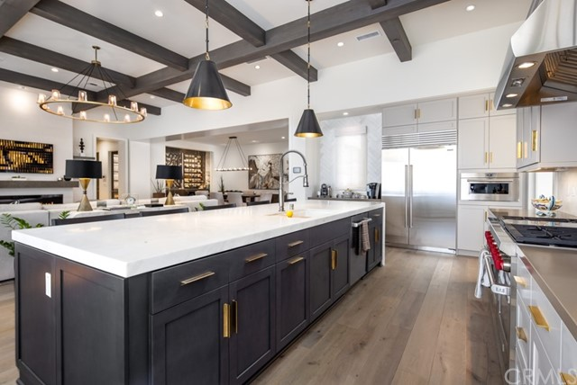 View of kitchen and great room plus dining room & wine room. Please note that this photo shows a completed, private residence. Buyer of the available home at 33 Thorsen Ranch Road will have the option to select interior finishes and colors as construction progresses.