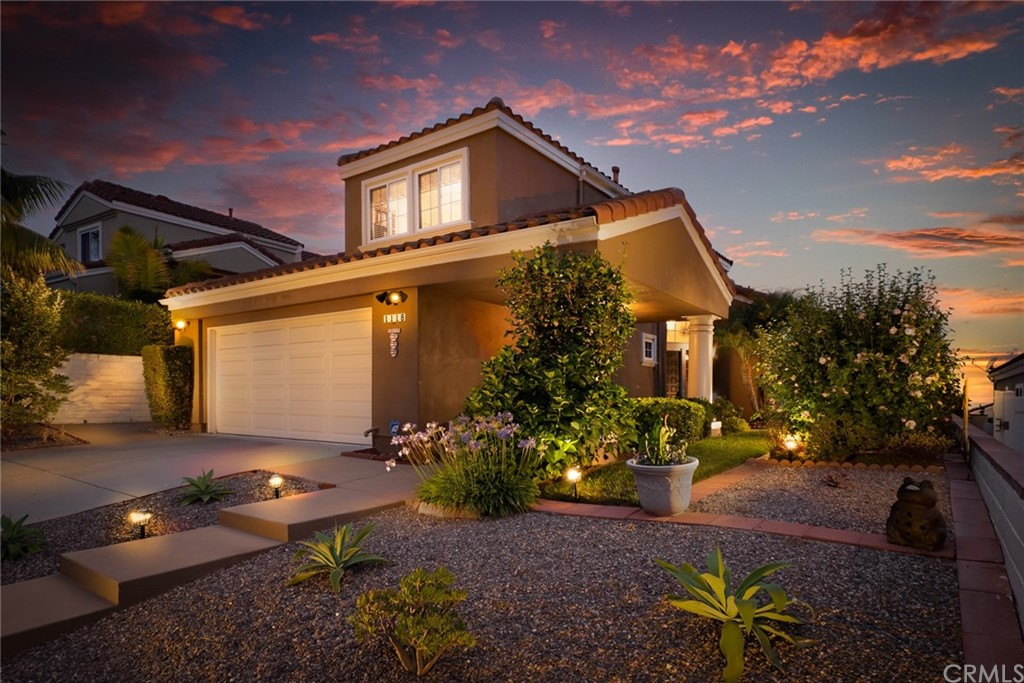 Enjoy OCEAN VIEWS, SUNSETS, and often CATALINA ISLAND from the backyard, and OBSERVATION DECK.  This perfectly situated home on a single loaded street in the wonderful and serene neighborhood of Bella Vista!  You'll love the low-maintenance front yard with a covered and lit walkway that leads you into this 3-bedroom, 2.5 baths featuring a MAIN LEVEL MASTER SUITE.  Upon entering you'll notice the grand staircase, high ceilings, and gleaming laminate floors that flow throughout most of the first floor. The open floorplan is ideal for entertaining.  The large MASTER SUITE is conveniently downstairs and offers a vinyl sliding glass door with direct access to the backyard so you can enjoy the ocean breeze. An adjoining spacious bathroom with dual sinks, a soaking tub, and a walk-in shower with a sit-down shower bench. The master bath also has a ceiling fan and a skylight to bring in the natural sunlight and offers two large mirrored closets, one of them being a walk-in. Enjoy the formal living area with vinyl picturesque windows, and French doors that lead to the backyard with the adjacent dining room which is perfect for your holiday dinners. The sunny kitchen features a breakfast bar and stainless-steel appliances, with Corian counters, handsome Cherry wood cabinetry, plenty of storage, a convenient pantry with pull-outs, plus a cheery window to look out of.  The kitchen easily flows into the comfortable family room with a ceiling fan and a gas fireplace. Inside laundry with direct access to the two-car attached garage, a large guest closet, and powder room complete the lower level. Step upstairs to find two sizeable bedrooms with ample closet space offering plenty of privacy for guests and family members Each room is well-appointed with a ceiling fan plus a spacious full bathroom with dual sinks, shower, and tub.  The linen storage area has been updated with newer Cherry cabinetry.  Relax and rejoice while you take in the VIEWS as you sit outside in the OBSERVATION DE