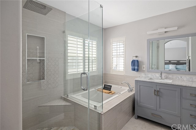 primary bathroom featuring shower, soaker tub, and double sink vanity