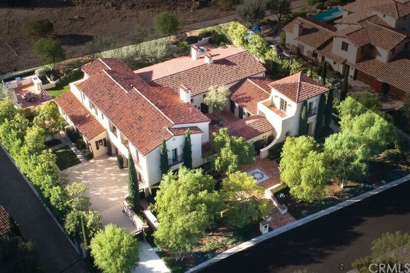 Behind the gates of exclusive Shady Canyon is a Spanish Colonial Revival Hacienda that will take your breath away! This perfect 'Old California' home is an exquisite balance of rich tradition & charm, blended w/the modern facets of life. Step through antique front drs into a 'room-like' courtyrd flooded with OC sunshine, low fountain, characteristic FP & flanked by rows of Loewen French Drs. The division of space is magical w/ground level mstr suite & bath, a hallway of horse shoe arches to a separate guest suite & upstairs play/exercise or office. This wing is anchored by a long wide great rm w/massive FP & defining touches of texture & color on every surface. Beyond this intricately tiled space is an expansive satin smooth wood bar where guests can chat w/the cook, a kitchen that simply defies your imagination & a rm that will be your favorite-a dining rm w/3 walls of windows & amazing light, an impressive office, ½ bth, perfect laundry & a butler's pantry. The wide wood & authentically tiled stairs ascend to the 2nd floor w/2 sumptuous guest suites, another laundry, half bath & fabulous lrg game room.  The balconies overlook the gorgeous gardens, 4th FP, tiled triple fountain, Jacuzzi & lush rose arbored walkway. There is no way to accurately describe the extraordinary focus on details that bring the past & the present together in such an astonishing way.  See supplement attached for a list of features & incredible upgrades that are the embodiment of beauty, form & design!