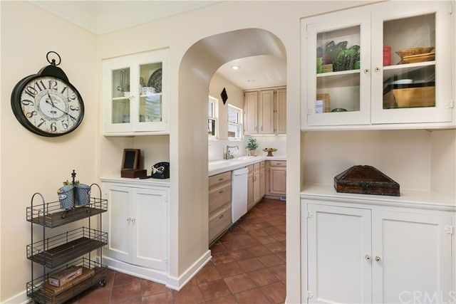 Breakfast Room featuring Dual Built-in Hutches with Glass Front Doors and an Arched Doorway to the Kitchen