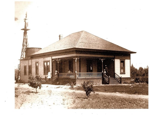 Early photograph of the house. Note the occupants on the front porch. The background appears to show a wind-driven water pump and water storage cistern - both of which are no longer on the property.