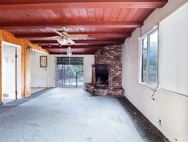 View of the open beam ceiling and fire place in the family room.