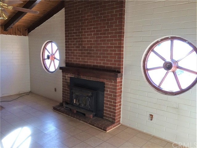 Living room, wood-burning fireplace, wagon wheel windows, tile flooring, wood ceilings