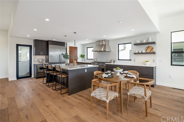 Central kitchen with bar seating, breakfast seating and adjacent dining area (shown here using reverse of 961 Unit A staging)