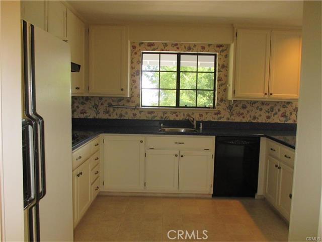 Kitchen has dishwasher, refrigerator , range, garbage disposal, pantry and a view.