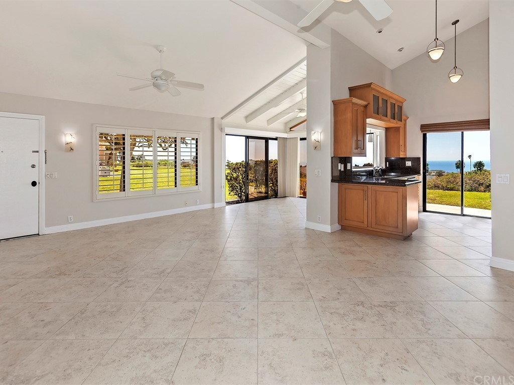 Fabulous panoramic ocean views from most rooms. This feels like a single family home with great privacy, long driveway, high ceilings and more. Complete previous remodel  with newer everything throughout. Newer dual pane windows, sliders, shutters, furnace and ducting, stainless steel appliances, granite counters, newer fixtures, scraped ceilings, newer water heater, newer interior doors, locks, 5 ceiling fans, custom lighting and much more. Floorplan has been enlarged with enclosed dining area/atrium. Extensive use of 20' travertine look porcelain tile on floors and neutral designer carpets. 2 car garage w/direct access and long driveway.
