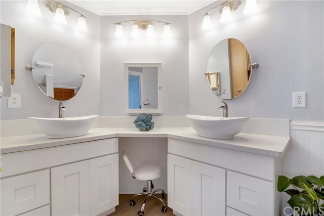 Master Bath features beautiful lighting, Double Canoe sinks and a Vanity area