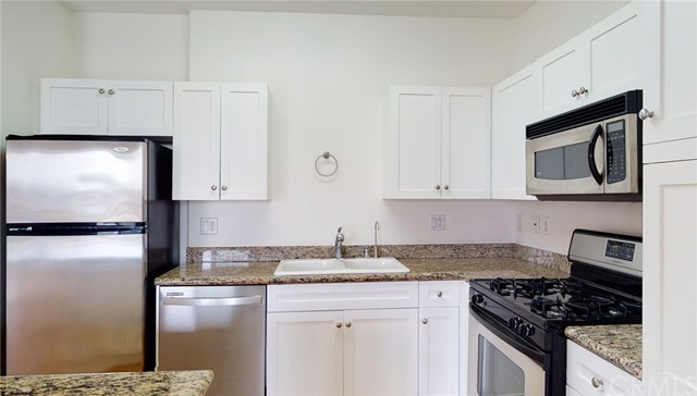 Kitchen equipped with refrigerator, dishwasher, microwave, stove, and reverse osmosis water system