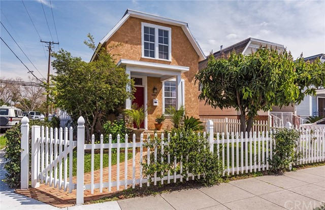 Welcome to 5994 Myrtle Ave, in the Houghton Park Neighborhood, corner lot. This home was originally built in downtown Long Beach in 1906 & moved to the current location. The nicely landscaped front yard has mango & myrtle trees, planter area, large porch with stone pillars, and wide yellow brick walkway, enclosed by a white picket fence covered by jasmine. Upon entering the house you walk into a large living room w/ high ceilings, large windows w/wood blinds. The open kitchen area is the centerpiece of the house, featuring new hickory cabinets, custom cut Mari Blue granite counter tops and large island w/ custom fluted tigerwood pedestal supports. Under cabinet LED lighting provides the area with an enchanting evening glow. The modern kitchen also has a newer stainless refrigerator, range & dishwasher & under cabinet microwave. The upgraded bathroom has a new vanity & tub-shower. Upstairs has 2 bedrooms w/ ceiling fans, new carpeting & large closets, one fitted with multiple drawers. Back down stairs past the kitchen is a walk-through closet area leading to the master bedroom & bath. One window overlooks the cascading rock water fountain - very popular with local avians. The other window overlooks the patio area. A large sliding glass door opens to the fountain & patio area w/ 2 guava trees, a peach tree, a lemon tree. A six foot block wall provides lots privacy. At the rear of the lot is a 2 car garage with automatic door, laundry area & workshop. Welcome to your new Home!!!