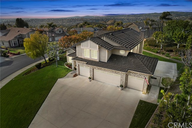 Welcome Home to this rare find in the Prestigious and Coveted Belsomet Community!  You can have it all with this unique, elusive combination of privacy, land, and views.  As you drive to the top of the hill, through the guarded gate, down the cul-de-sac you will find this elevated estate on nearly ¾ of an acre affording views of rolling hills, city lights, and breathtaking sunsets!  Walking through the double door entry, you're greeted with soaring ceilings and a curved staircase, relaxing as you look through your first wall of windows and take in your large, green lawns that afford privacy and calm.  The chef's dream kitchen is also flanked by windows and has a Sub-Zero refrigerator, expansive center island, an abundance of food prep/storage areas, and an extra deep pantry.  The kitchen opens to the family room featuring a custom stone wall/hearth, cozy fireplace, and a wall of windows that connect you with your expansive backyard retreat.  Upstairs is the primary suite boasting beautiful city night views and a relaxing jetted bathtub.  Other amenities include an oversized bonus room/6th bedroom with built-in entertainment center, 1 bed/office on the main floor, custom interior 3-light frosted glass doors, California Closets custom mudroom, plantation shutters, whole house attic fan, hot water recirculating system, 4 car garage with epoxy coating, and a side yard for a sport court.  This huge serene lot offers room to create your own paradise or make other dreams come true.