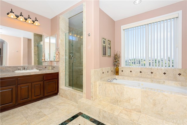 Master Bathroom with custom walk in shower, Spa Garden Tub, Separate His and Hers sinks with Granite counter tops and custom marble tile flooring.