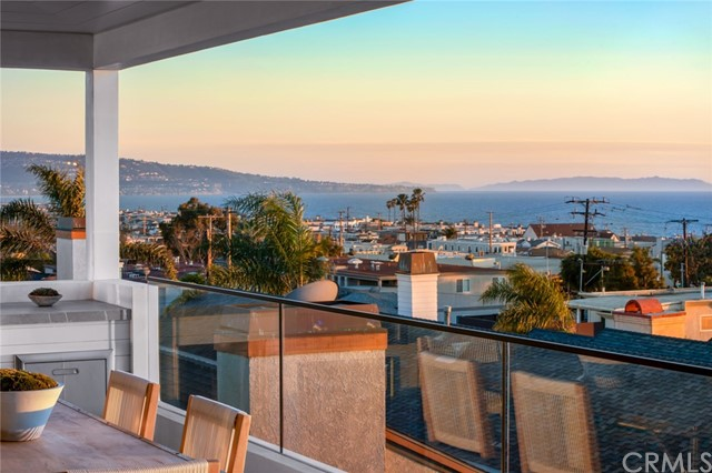 Coastal essence with a contemporary California Twist in this corner lot location. In a rare area of 30' high limit, 1 block from downtown MB in American Martyrs offering HUGE PANORAMIC 180-degree OCEAN VIEWS that lends itself to a beach resort lifestyle amid a striking surround. Unimpeded ocean vistas through the views that pan CATALINA, Palos Verdes, Santa Monica Mtns to Malibu. Perfect for entertaining with its top floor of living space designed completely open with the kitchen, dining room, family room & living room. European white oak floors, 5 beds or 4 w/office, 4 living areas, flex room on the first floor, a MEDIA ROOM with Bar on the lower level. Elevated light fixtures by Ralph Lauren, Thomas O'Brien, and Arteriors Home with a modern flair. Kitchen has a massive 12-ft island, 6 burner Wolf range with griddle and double ovens, Wolf microwave & steam oven, 2 wood-paneled Bosch dishwashers, wood-paneled Subzero refrigerator & Subzero wine fridge. Dornbracht & Grohe plumbing fixtures, Neolith slabs in kitchen, master bath counters & shower. Master bath has a jetted tub, & Mr. Steam shower. Extensive use of marble, quartz, limestone, retro marble Neolith, subway and glass tiles throughout the home. Other amenities are prewired Creston and for automatic data, phone, cameras & auto shades, 4 STOP ELEVATOR, wine closet, each bedroom has an en-suite bath, the HVAC is 3-zoned, Cape Cod ship lap siding walls inside and out and Solar ready roof, 2 master closets and much more.