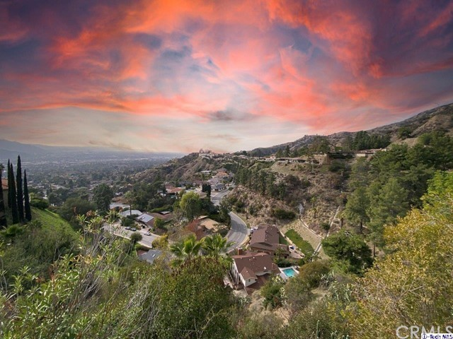 Opportunity awaits with this traditional view home perched in the exquisite Rimcrest area of Glendale!  With views from every room, Wonderview is notorious for its privacy, pride of ownership and great neighbors throughout.  This home has an expansive deck with sweeping views that overlook San Fernando Valley, Burbank, Glendale and Los Angeles.      On the first floor, there is a generous sized family room with fireplace that flows through to the kitchen, breakfast area and dining room.  With a split second story, one portion offers 3 bedrooms and two baths while the other has a large room with a 2nd fireplace which can also serve as a second master retreat (4th bedroom).  The exterior grounds include an expanded wooden deck and vegetation extending to the street below.    The property is in need of a tasteful upgrade throughout.  Priced at only $433/ft, this home provides a rare opportunity to a family or investor to upgrade this home to a splendor that will be enjoyed for many years to follow!