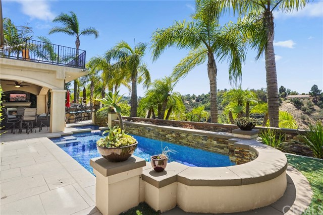 Model perfection!  Beautifully appointed view residence enhanced by elegant designer touches, Elan home system, and outdoor oasis.  Desired great room concept living at its finest! Italian wood-like tile flooring and walls of glass provide the backdrop to this highly customized kitchen with expansive center island dressed in sleek quartz counter tops, custom cabinetry with glass door fronts and pull outs, top of the line appliances including Miele, Subzero, and Wolf six-burner range with custom wood range hood, built in refrigerated wine storage and drawers all open to the rear yard and extensive family room boasting custom entertainment center, dry bar and quartz accented fireplace. Welcoming you upon the second level is the airy bonus room with built-in desks and media base cabinet, access to the master suite and three spacious secondary bedrooms, one a complete en-suite. Beyond the double door entry the master suite offers a private viewing balcony, an inviting slate infused master bath with dual vanities, bubbling Jacuzzi tub, shower and dual walk in closets. Professionally designed backyard includes a covered entertainment pavilion with fireplace, BBQ island bar and ledge stone accented pool and spa with serene spillways. Offering a masterful floor plan, amazing tranquil views of hills and distant city lights, over sized four car garage and situated in the desirable guard gated community of Belsomet this home is not to be duplicated.