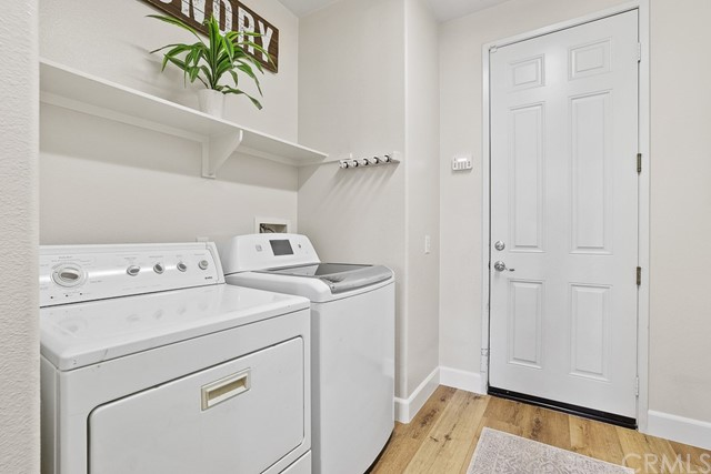 Spacious laundry room with new LVT flooring, freshly painted, and shelving space.