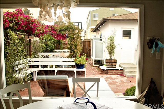 Looking out at charming patio/yard area from inside dining area. Garage is on right and is a 2 car garage with alley access.