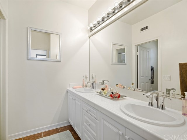 Secondary bath with dual vanities and private shower and commode.