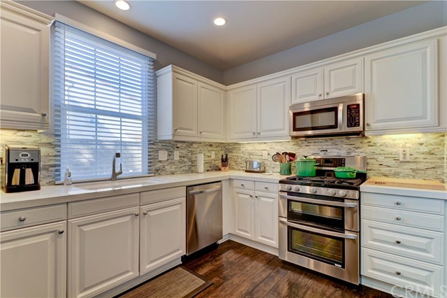 Inviting kitchen with timeless white cabinets, quartz counters, tile backsplash and stainless steel appliances