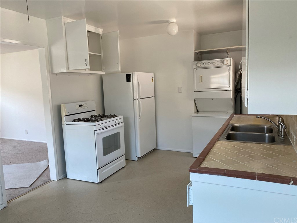 Kitchen including gas stove, refrigerator and stacked washer/dryer