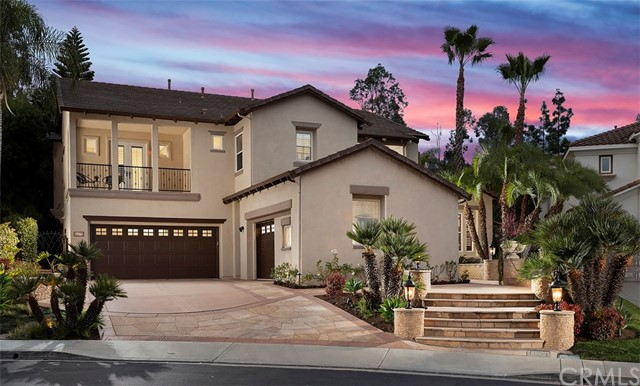 Fresh high-end upgrades, an impressively sized floorplan, and a world-class resort-style backyard unite to create custom-caliber luxury living at this grand residence behind the guarded entry gates of Treviso at Tustin Ranch. No expense has been spared at the home, which reveals a tropical oasis with new putting green, a fireplace, custom BBQ island, and a magnificent saltwater pool and spa with rockscapes, a waterfall and waterslide. Dual staircases in a two-story entry provide the ideal introduction to the sophisticated residence, which is graced with fresh paint, travertine flooring, crown molding and new window treatments. A newly expanded great room offers a bar with wine refrigerator, a secondary staircase, and a brand-new state-of-the-art entertainment system with 7.1-channel Dolby Atmos surround sound, in-ceiling speakers, floating cabinetry, and a new Control4 entertainment and smart-home automation controller. The adjacent kitchen shines with new quartz countertops, on-trend white cabinetry, a walk-in pantry, nook, an island and a new built-in Sub-Zero refrigerator. A new home security system features cameras and a Ring doorbell. Four bedrooms and 4.5 remodeled baths are featured, including a first-floor bedroom, in approx. 4,648 s.f. Discover an office, a deck and separate balcony overlooking the front yard, and a master suite with circular foyer, a sitting area, 3-sided fireplace, dual walk-in closets, in-ceiling speakers, a large shower and separate soaking tub.