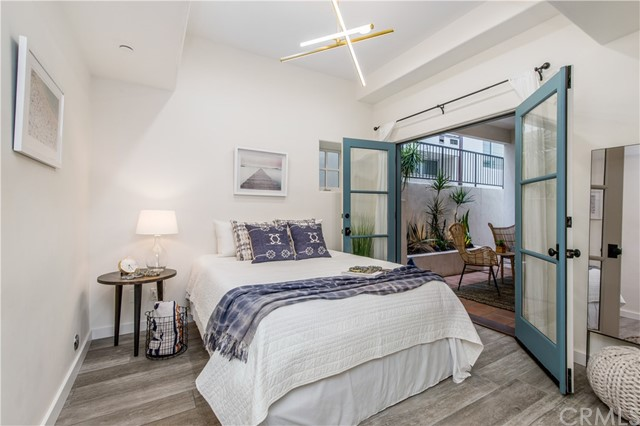 Sunny and bright guest bedroom with Italian wood-look porcelain tile and French doors leading to an outdoor patio.
