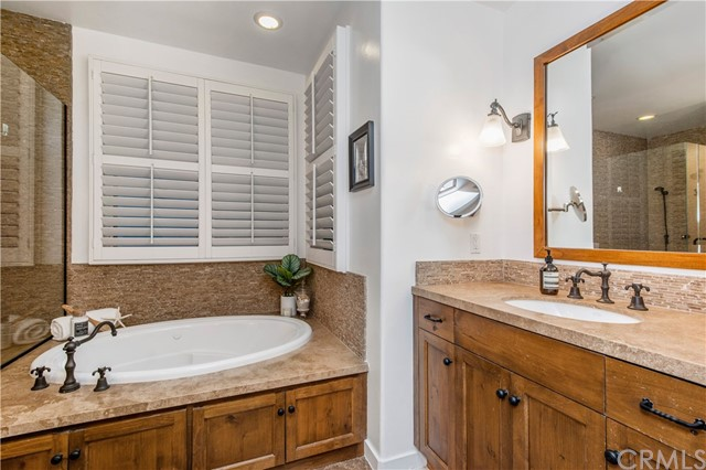 Plantation shutters surround the spa-like tub in the Master bathroom.