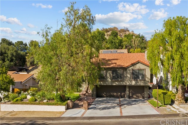 """Situated in the prestigious Rancho La Salle Gated community of 52 acres, only 25 large-lot homes sit on this cul de sac.  For the first time on the market, this customized home has been enlarged to add more livable space.  Custom brick hardscape and lighted pilasters welcome you to the home.  This split-level home has an indoor atrium creating a """"wow-factor"""" when you first enter.  This adds plenty of light & brightness. Beautiful leaded glass front door & sidelight open to a large living room with soaring ceilings, brick fireplace and large picture windows.  There are ceiling fans throughout the home. The Family room has wood flooring, vaulted ceilings with French sliders that take you out to the back patio and pool. Kitchen is open to the raised dining room with wood flooring and an overview of the living room.  The large Kitchenaid Refrigerator stays with the home.  There are custom oak cabinets, tile counters with a serve through counter to the Family room.   Besides the numerous bedrooms and bathrooms, you have a gym and a large bonus room with a fantastic stone & brick fireplace with a raised hearth, large picture windows, window seat, wet bar, raised area for pool table–which is included—and a spectacular wood vaulted ceiling.   The large private Master suite is on its own level with walk-in closet and huge master bath.  You have an indoor laundry room with sink and counterspace plus the newer washer & dryer are included.    There is a newer water heater, solar panels, entry to the 3-car garage is from the lower level, plus ample space for parking.  You have dining and lounging in the back yard with a child-safe pool that has a waterfall/slide with custom brick & stonework. Beautiful Oak trees.   Wonderful private area to entertain, relax and play.  Commuters--enjoy the quick access to the 5 Freeway.  Great schools, great shopping and entertainment very close by.  No Mello Roos.  Homes rarely come up for sale in this gated community."""