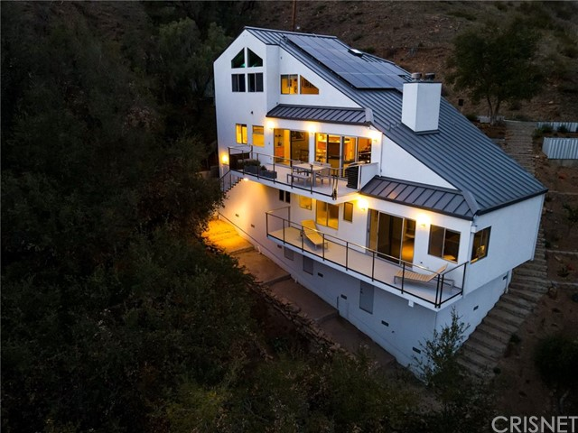 Tucked in the El Nido neighborhood, The Nest, above Malibu's Corral State beach, is this one of a kind 2013 contemporary home nestled in mature oak trees on three parcels of land. To appreciate this home, one must value the feeling of a cool sea breeze, the ocean air, and a peaceful lifestyle that comes with natural surroundings. The entry to this multi level, 3+ bedroom potential  home, pulls you in with the allure of the exposed high wood beamed ceilings. A fully functional sound studio allows the creative musician to write powerful scores, with opportunities to convert to a top of the line screening room or secondary guest quarters. Grey natural stone stairs guide you to the main level with thoughtful architectural lines and an open floor plan. The Fleetwood sliding doors invite you to experience dinner in the trees on the main-level balcony, while taking in sunsets with indigenous birds in flight over the canyon. Oversized master suite is a true daily escape featuring high-ceilings, warming fireplace, updated bathroom with natural wood cabinets, glass shower, spacious tub, and ample space with walk-in closets and storage room. Secondary bedroom features natural wood flooring with an updated full bathroom.  Kitchen comes with granite counter tops and high end stainless steel appliances. An opportunity to be part of a truly magical community surrounded by the canyon, ocean and nature. Relax, breathe deep and re-energize while enjoying the El Nido lifestyle on Vista Mar.