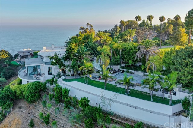 $2 MILLION PRICE REDUCTION! Located in coveted Serra Retreat, this gated community provides the best of what Malibu offers-natural beauty, privacy, security and convenient beach access. The Estate at 3464 Sweetwater Mesa Road was completely reimagined at the end of 2018. and sits on 4.2 acres, boasts whitewater views of the beaches below, coastline vistas and a panoramic view of the Queen's Necklace. The 7,900-square-foot home is accessed via  a gated private driveway framed by palm trees. The property features an immense amount of natural light, soaring ceilings, 6 bedrooms and 7 bathrooms. Every corner of the estate is designed to epitomize SoCal's indoor-outdoor lifestyle. Interior features include ensuite bedrooms, a wine cellar and a home theater. In the backyard, find a zero-edge pool, spa and cabana. For even more incredible views of the Pacific, ascend the home's exterior staircase to the more than 3,000-square-foot rooftop deck. Though it is designed to be a tranquil oasis, Sweetwater Mesa is moments from popular shopping and dining spots.