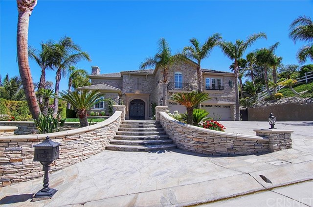 Beautiful Sand Canyon Estate! This Mediterranean style estate is a must see! Fully remodeled inside and out, this turn-key home shows tremendous pride of ownership!  Custom stone work and hardscape and the expanded drive way and 3 car pull-thru garage leave plenty of room for RV parking.  The gated front door opens up to an impressive staircase and crystal chandelier in the foyer. The living room leads to  the adjacent formal dining room and piano room/library. The spiral staircase opens up to a Romeo and Juliette balcony.  The large primary bedroom has custom stone and wainscoting and a large newly remodeled bathroom complete with jacuzzi tub and chandelier and his and hers closets. The rec/movie room is large enough to accommodate friends and family for a game of pool or movie a night. Large family room and chefs kitchen are perfect for entertaining! Large double islands, bold crown and wainscoting and hand painted Italian tile backsplash along with the Viking appliances and custom cabinetry make this a chef's dream! Wait! if you like to entertain then you have to come see this backyard! Large covered patio covers the outdoor living space which includes a built in barbeque, TV, fireplace and ceiling fans. The resort style pool has just been refinished with new plaster and tile and boasts 2 jacuzzi's, a grotto and a slide. Surrounding the pool is an enchanting yard with palm trees and grassy areas perfect for big parties. Plenty of storage, this home comes with a two story, fully finished  unattached garage with an outdoor bathroom, great for pool parties! Brand new full house generator runs the entire home and pool equipment if needed. Too many amenities to mention!