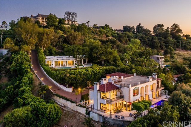 Perched on an ultra-private hillside on the coveted Mulholland Drive, this magnificent, gated, European-style villa captures panoramic views across the valley to the mountains. From the tree-lined motor court enter the foyer, where stately columns and archways lead to the ballroom-like great room, featuring 30' ceilings, glass doors, clerestory windows, 8' fireplace and Renaissance-style alfresco paintings. The chef's kitchen showcases modern design, quartz countertops, custom cabinetry, Miele appliances and breakfast bar. Open, airy living areas segue to the wraparound, hillside terrace with heated pool and spa. Five bedrooms include the stunning master with a dressing room and fireplace. Home features include an expansive rooftop terrace with 360-degree views, marble and hardwood floors, lush gardens, stone fountains, library and 3-car garage. An entertainer's retreat, the residence offers the utmost privacy and serenity in one California's most iconic and desirable locations.