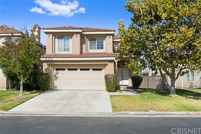 """Located in a gated community of Santa Clarita, with beautifully built residents, is a 2139 sqft, 4-bedroom, 2.5-bathroom, single family home. This large space is ready for the next lucky buyer to call """"home"""". Landscaped with a neat lawn, a paved walkway leads to the double door entry. Upon entering you are greeted with high ceilings and tile flooring all throughout the home. The lengthy living room is luminated with natural lighting from all the surrounding glass windows, giving the space an airy feel, with the perfect touch of coziness from the fireplace. An easy flow to the eat in kitchen which includes tile countertops, built-in appliances and an easy flow to the family room, making it the perfect venue to entertain guests. A hallway at the right of entry that leads to a closet for the washer/dryer hookup and a half bathroom for the convenience of guest. Ascend to the second floor that connects a bathroom with 3 bedrooms, all of which include carpet flooring and built-in closets. A primary at the end of the hallway which includes a walk-in closet and an en suite bathroom. Access to a backyard from both the living room and the kitchen, to set up for lounging and to enjoy the views of Santa Clarita's mountains. Home includes an attached 2 car garage with direct access from the house that can also be used as a nifty workshop."""