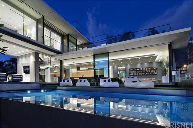 Perched high in Hollywood Hills West above the Sunset Strip, this striking 5540-sq-ft modern masterpiece is an ode to glass, space, and sightlines. Envisioned by renowned bicoastal architectural firm Fu Wilmers Design, 11-ft floor-to-ceiling vanishing doors, windows and glass- walled decks blur the barriers between inside and out, showcasing jetliner views that span from city to ocean to mountains across an infinity-edge pool. Each angle displays superior materials, from the full Miele kitchen to German Badeloft fixtures, within a flowing open layout and chic neutral palette. There are 5 spacious bedrooms, 7 baths, and a skylit lower-level flexible entertaining space with a bar, gym, wine room and a Dolby Atmos theater; it's an integrated smart home as well. Built just in 2018, this extraordinary property is now fully realized in every aspect, from its impeccable landscaping to its newly finished wooden rooftop decks. Rise above it all and live above it all in this unforgettable oasis.
