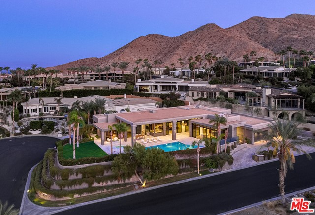 Situated minutes away from the Ritz Carlton Rancho Mirage, this remarkable contemporary estate w/panoramic mountainscape views is one of architect Sam Cardellas masterpieces. This four bedroom five bath property possesses high ceilings accompanied by illuminating glass sliding doors, a large swimming pool overlooking the valley and exquisite finishes. The customized gourmet kitchen has finished African Wenged & Teak cabinetry and a built-in coffee machine w/wok counter that opens up to the outdoor living room patio and pool. Adjacent is the indoor living room, which contains a bar forged from exotic Costa Rican granite, perfect for entertaining family and friends. The master suite boasts explosive views of the San Jacinto Mountains & possesses two separate ensuite baths w/an adjoining office, ideal for working at home. The three junior suites have floor to ceiling windows & doors to access outside. Pull into the air-conditioned, three car garage to begin your luxurious desert retreat.